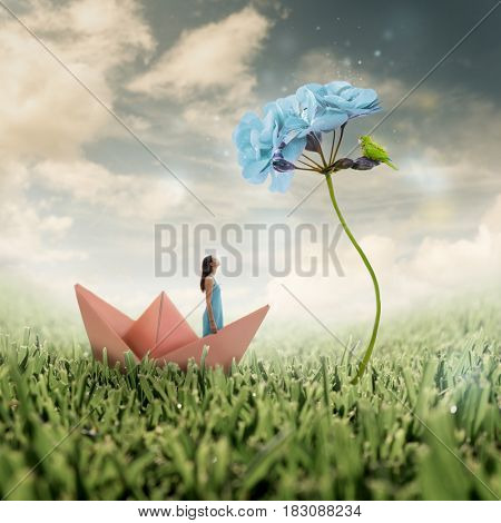 Pretty girl in a pastel colored dress looking up to an enlarged bright blue flower with a green parrot