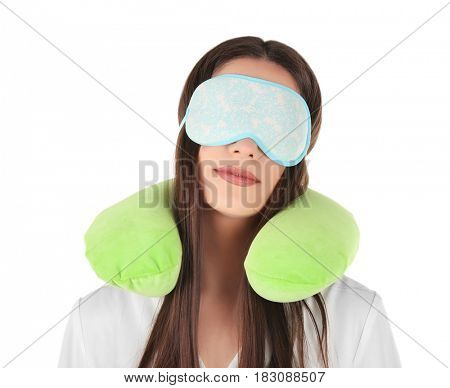 Beautiful young woman with travel pillow and sleeping mask on white background