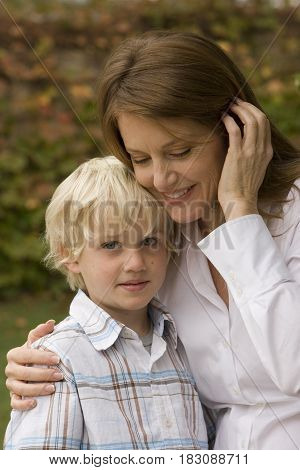 Happy mother hugging her son outside at the park.