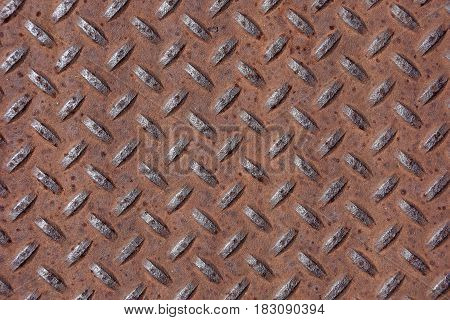 close up of rusted diamond plate manhole cover