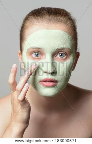 Girl with green cream on face. Beautiful young woman applying facial homemade mask at home.