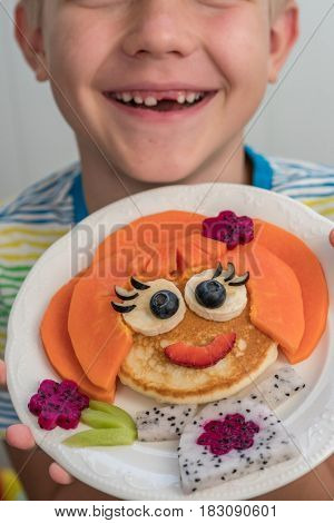 Funny girl pancake face with fruits and berries