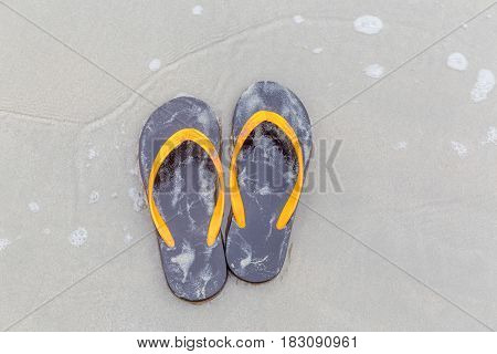 Brown and orange beach slippers soak in ocean water summer vacation concept.