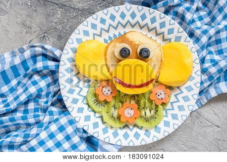 Funny monkey pancakes with fruits for kids breakfast