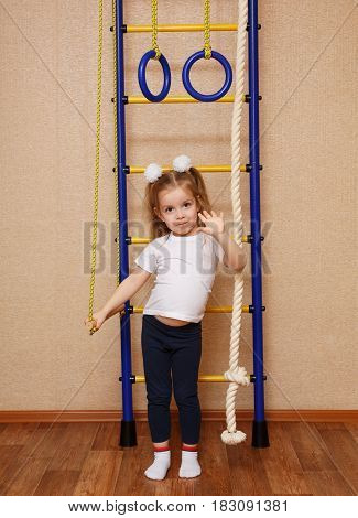 Little girl in sport clothes standing next to wall bars. The concept of a healthy lifestyle from a young age. Children's sports.