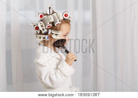 Little girl fashionista. Girl in curlers and a robe holding a makeup brush. Little coquette posing. Human emotions. She does make-up.