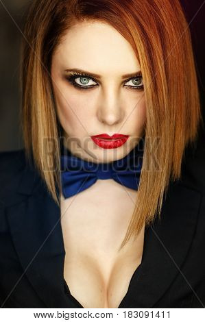 Young attractive girl in a jacket and bow tie looks languidly. Femme fatale. Evening makeup smokey eye. Expressive eyes