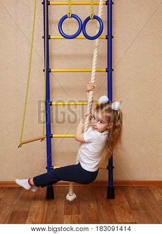 Little girl in sportswear riding on a rope on the wall bars. The concept of a healthy lifestyle from a young age. Children sport.