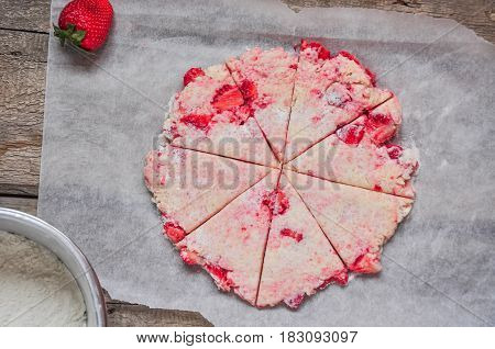 Strawberry scones dough cutted into segments on a parchment paper. Preparation for baking fruit scones. Top view and rustic style. Wooden background.