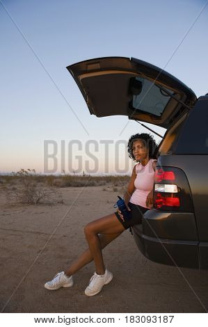 African woman sitting on back of car