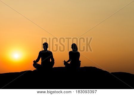 Silhouette Of Attractive Confident Half Naked Man And Woman Doing Yoga On Beach Rock