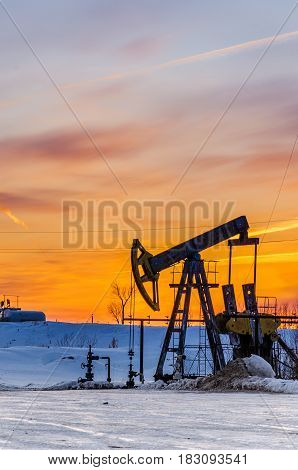 Pump jack and wellhead during sunset in the oilfield. Winter period. Oil and gas concept.