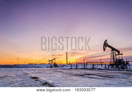 Pump jack, wellhead, pipeline and oil rig during sunset in the oilfield. Winter period. Oil and gas concept.