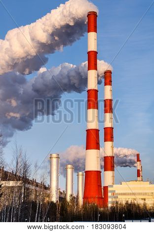 Gas power plant in sunny day. Pipes with smoke. Energy industry concept.