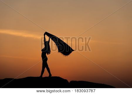 Silhouette of half naked confident woman man doing a freedom pose against the sun on rocky ground on a sun set sky near beach for wining achievement freedom overcome result performance concept