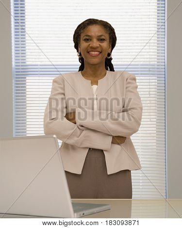 African businesswoman standing by desk