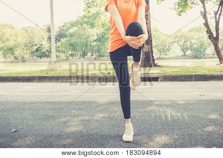 Attractive Confidence Asian Woman Runner Doing A Leg Stretch Before A Run