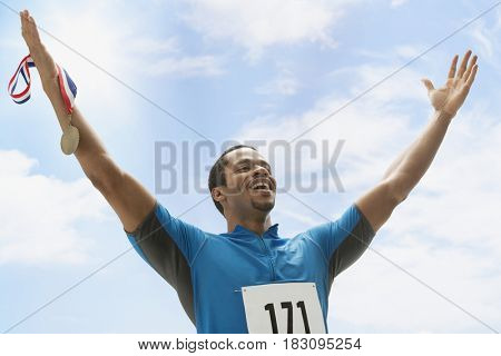 Mixed race athlete holding medal with arms raised