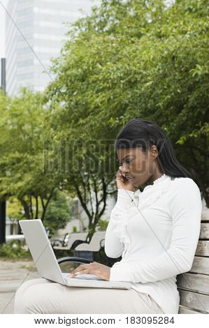 African businesswoman using laptop on bench in city