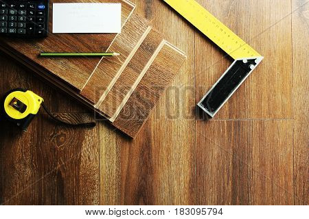 Laminate floor planks and tools on wooden background.