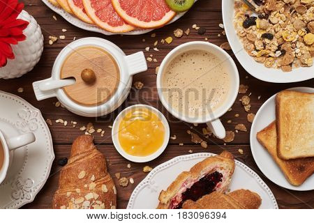Flat lay picture of carbohydrate breakfast on wooden wretched background. Cup of coffee and honey. Yummy food
