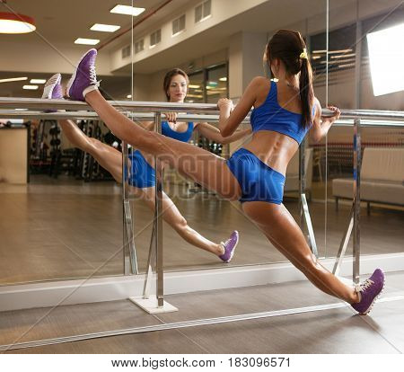 Female with nice body warming up and doing stretches a the gym