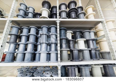 Gray and white plastic reels stand on the shelf.