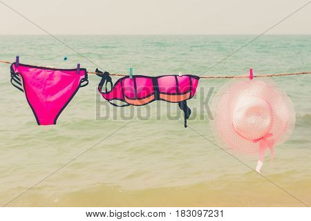 Retro pink bikini and vintage pink hat hanging on rope against the sea with vintage retro filter effect for exotic holiday romance relaxing vacation concept