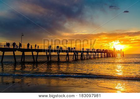 People walking along Glenelg Beach jetty at sunset Adelaide South Australia