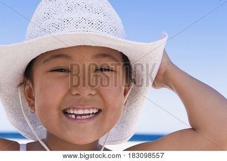 Eurasian girl wearing sun hat