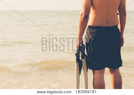 Beautiful attractive young asian man posing portrait on beach holding scuba diving fins gear vintage retro filter effect for exotic holiday romance relaxing vacation concept