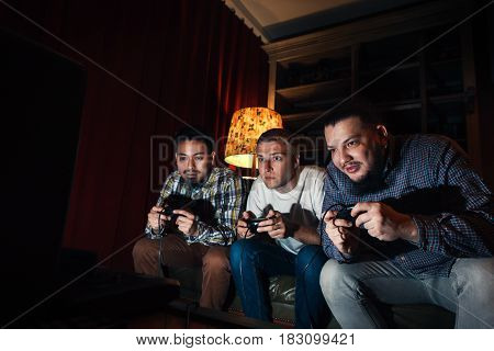 Three high concentrated young guys with joysticks play exciting video game at home in dark room. Tension to win tourney.