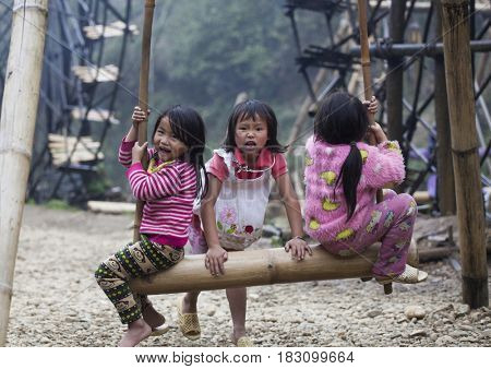 Sa Pa, Vietnam - 12 March, 2017: Ethnic minority, Hmong children playing on a swing in tradition village of Cat cat, Sapa, Vietnam