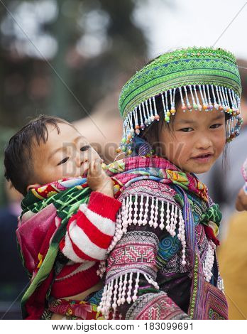 Sa Pa, Vietnam - March 15, 2017: Unidentified Hmong girl carrying baby and wearing traditional attire in Sapa, North Vietnam