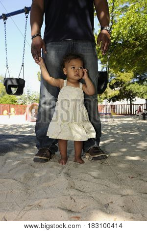 Father and barefoot daughter at playground