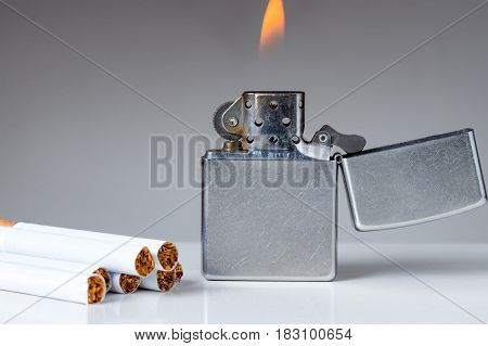 Cigarettes and lighter with flame on white and grey background. Nicotine and tobacco addiction abstract concept. Copy space on the left.
