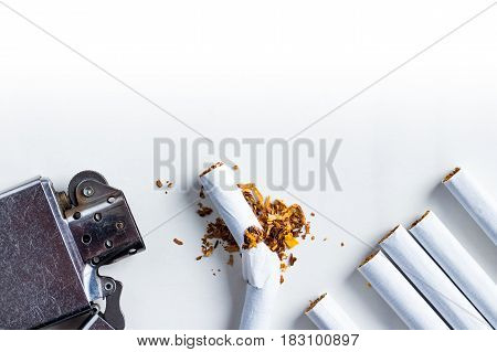 Bunch of cigarettes and an old scratched lighter. White background. Copy space on top.