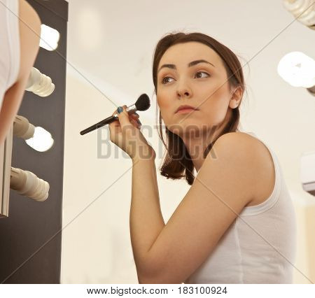 Picture of beautiful woman doing her make-up and looking to the mirror