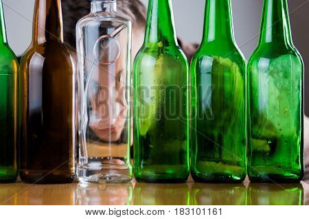 Sad young man behind green and brown glass bottles. Fighting alcohol addiction problem abstract concept.