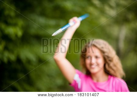 Young sportswoman holding up a javelin with a smile with focus to the sharp point of the shaft