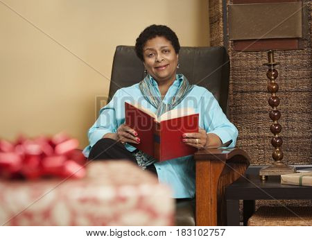 African woman reading a book in armchair