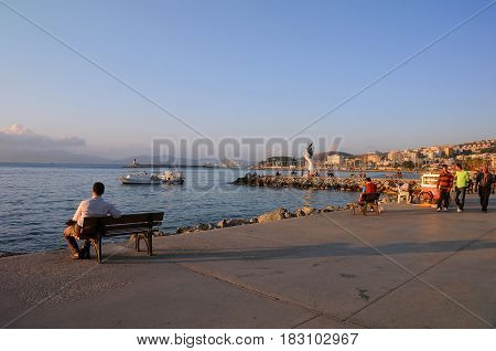 KUSADASI TURKEY - OCTOBER 4 2009: View of marina and Hand of Peace statue at sunset