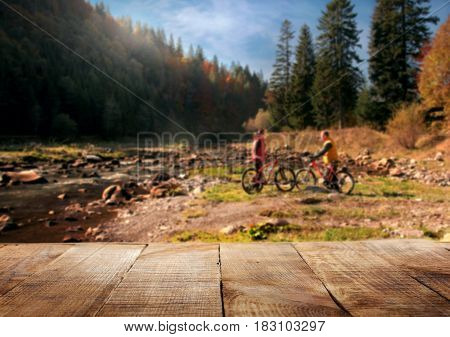 Wooden table against a blurred forest with couple of cyclists for product display montage