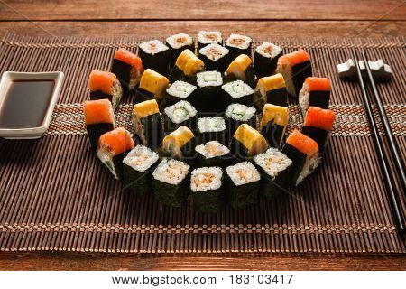 Bright colorful japanese sushi set, round ornament of maki rolls served on brown straw mat, closeup. Japanese food art, national cuisine, restaurant menu photo.