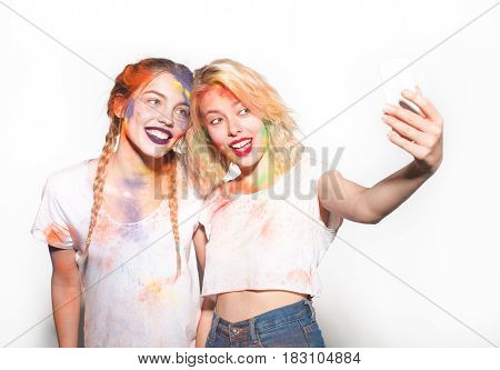 Two girls with faces painted taking selfie on white background.