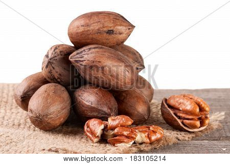 a bunch of pecan nuts on the old board with white background.
