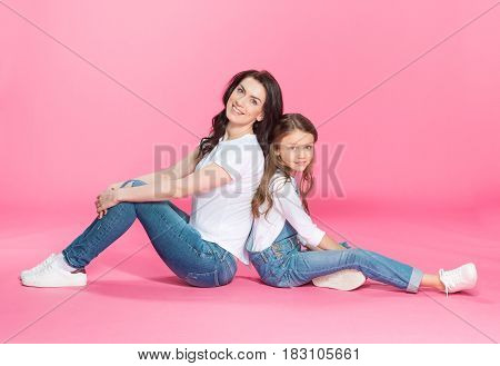 Happy Beautiful Mother And Daughter Sitting Back To Back And Smiling At Camera