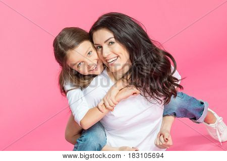 Happy beautiful mother and daughter hugging and smiling at camera