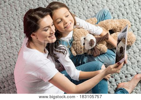 Beautiful Happy Mother And Daughter Sitting Together And Using Digital Tablet