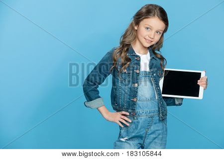Cute Smiling Little Girl Holding Digital Tablet With Blank Screen On Blue
